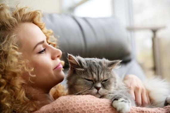 אישה מתכרבלת עם חתול על ספה